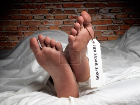 Photo pour Image drôle d'un homme qui se repose recouvert d'une feuille comme à la morgue, avec une étiquette sur son pouce. - image libre de droit