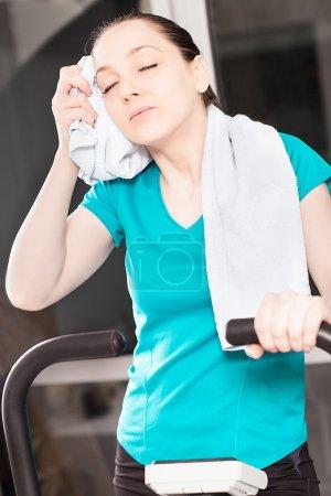 Photo pour Femme dans un studio de fitness est fatigué après l'excercise tout en nettoyant son visage - image libre de droit
