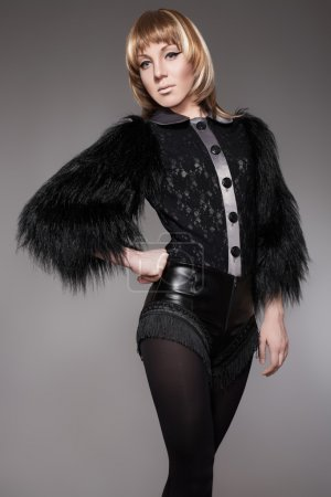 Beautiful woman model in fashion black clothes with fluffy fur and leather shorts. Boho style