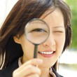 Asian business woman with magnifying glass to the ...