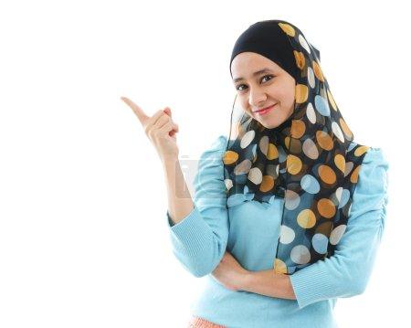 Photo pour Mignonne jeune femme musulmane pointant sur l'espace vide, isolée sur blanc - image libre de droit