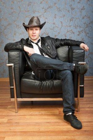 Photo pour Jeune cow-boy assis dans une chaise sur un fond de murs à motifs - image libre de droit