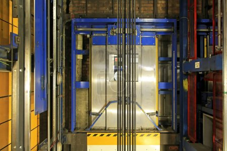 Modern elevator shaft interior with cables and tra...