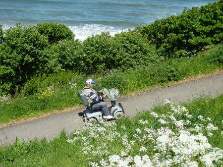 Photo pour Homme roulant sur scooter de mobilité vers le haut d'une colline escarpée . - image libre de droit