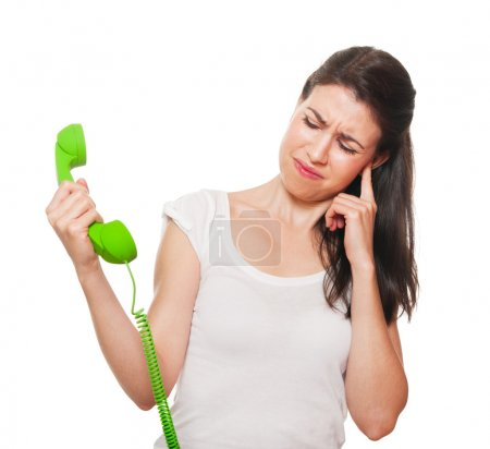 Photo for Young female getting stressed by someone on the phone. Isolated on white. - Royalty Free Image