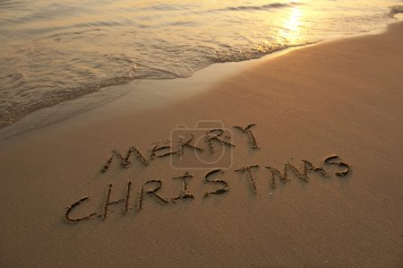 Photo for Merry Christmas handwritten in sand on beach - Royalty Free Image
