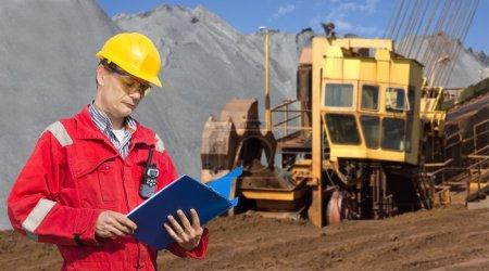 Photo pour Un contremaître dans un site minier, vérifiant les billes dans un dossier bleu, avec une énorme pelle à roue en arrière-plan - image libre de droit