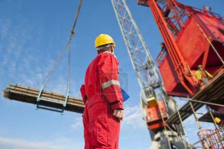 Foto de Operador de construcción mirando una grúa con andamios materiales a una estructura súper tamaño en un sitio de construcción - Imagen libre de derechos