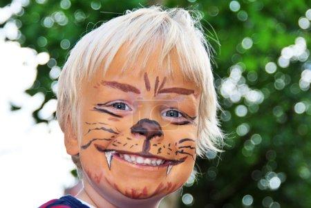 Photo pour Le visage souriant d'un jeune enfant peint pour ressembler à un lion féroce - image libre de droit