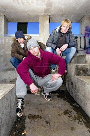 Photo pour Trois gangmembers de la recherche en colère dans un bunker sale, béton au crépuscule. - image libre de droit