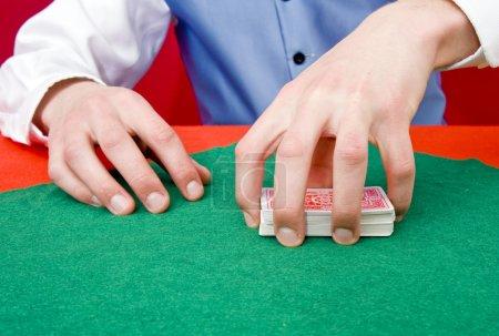 Photo pour Un concessionnaire saisissant un jeu de cartes poker - image libre de droit