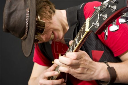 Photo for A trendy looking guitar player during a heavy guitar solo. Selective focus on the musicians left hand - Royalty Free Image