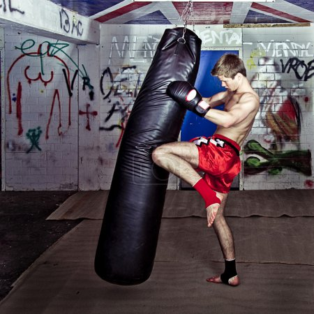 Photo for Athletic muay thai boxer giving a forceful knee kick during a training with a boxing bag - Royalty Free Image