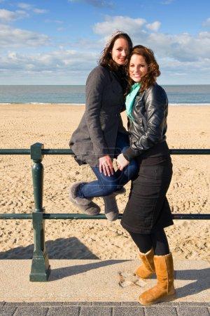 Photo pour Deux amis posant à la plage par un bel après-midi d'automne - image libre de droit