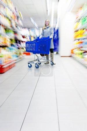 Photo pour Femme confiante avec son caddie dans un supermarché, faisant épicerie - que choisir - image libre de droit