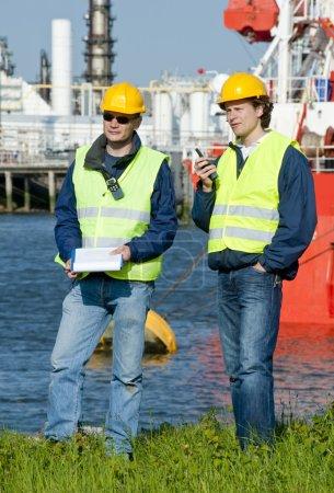 Photo pour Deux ingénieurs portuaires avec des radios, un équipement de sécurité personnelle et un panneau clip - image libre de droit
