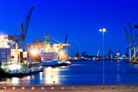 Photo pour Image d'un port de la ville avec une couleur saturée bleu intense. Les bateaux sont sur l'eau, et la ville de Rotterdam est visible en arrière-plan. Non. Plan cadré horizontalement . - image libre de droit