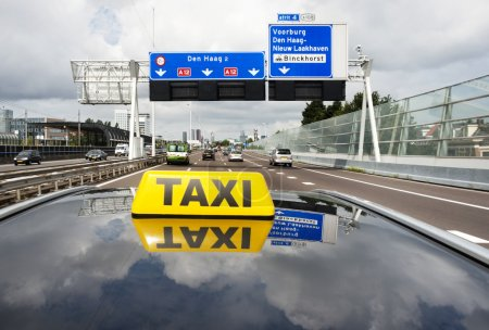 Taxi driving on a multiple lane motorway towards a...