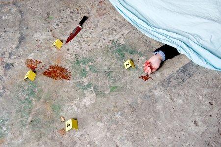 Photo pour Un cadavre couvert, d'une main sanglante qui sort de dessous le Suaire, entouré d'éléments de preuve : l'arme du crime, une empreinte sanglante et un mégot de cigarette - image libre de droit