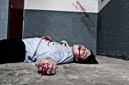 Photo pour Victime de meurtre gisant sur le sol, une balle dans un sous-sol, avec des éclaboussures de sang sur le mur. traverser transformés. - image libre de droit