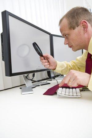 Photo pour Homme d'affaires sérieusement analyser les données sur un écran d'ordinateur à l'aide d'une loupe, avec son index gauche en vol stationnaire au-dessus de la touche Échap pour interrompre le processus. un tracé de détourage des moniteurs est inclus à la résolution maximale de l'image - image libre de droit