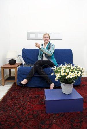 Photo pour Une femme assise sur un canapé dans une pièce faiblement décoré avec les jambes croisées, tenant un verre de vin après une longue journée de travail - image libre de droit