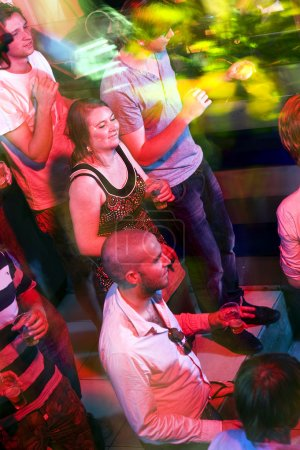 Photo pour Fête sur une piste de danse animée, engloutie dans les lumières d'une boîte de nuit - image libre de droit