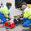 Paramedics and a fireman strapping a wounded woman...