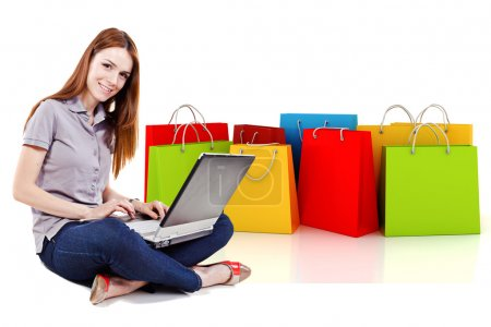 Young beautiful woman using a laptop for online shopping with 3d shopping bags in the background