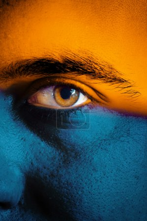Photo for Orange and blue flag painted on face of a sport team supporter, close up of a male eye. - Royalty Free Image