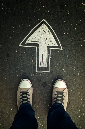 Photo for Male sneakers on the asphalt road with drawn direction arrow - Royalty Free Image