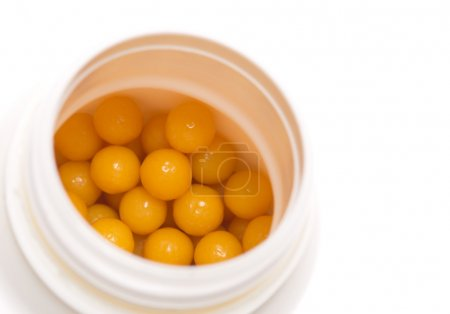 Yellow pills in open box