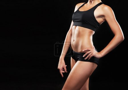 Photo for Young fit woman in sports outfit, black background - Royalty Free Image