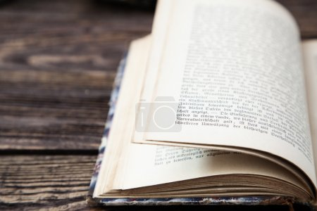 Photo for Aged open book on wooden table - Royalty Free Image