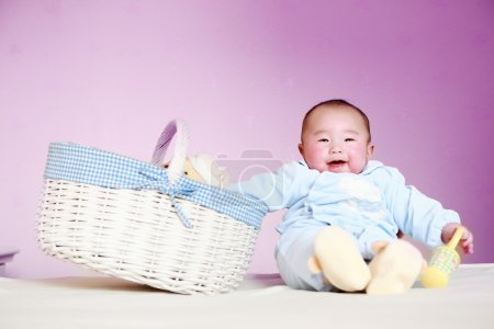 Cute baby sitting next to the basket