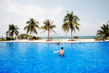 Swimming pool in china hotel with palm trees. chin...