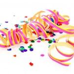 Colorful confetti and party streamer over white ba...