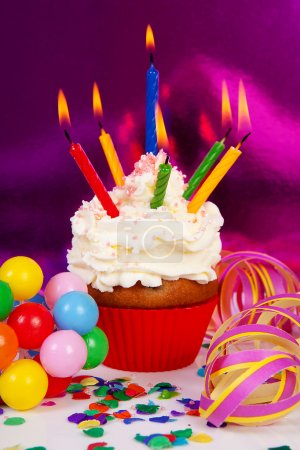 Photo for Birthday cupcake with lots of candles, party streamers and colorful confetti over purple background - Royalty Free Image