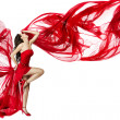 Woman in red dress flying on wind flow dancing ove...