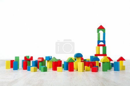 Photo for Building blocks toy over floor in white empty interior. Childrenroom design. - Royalty Free Image