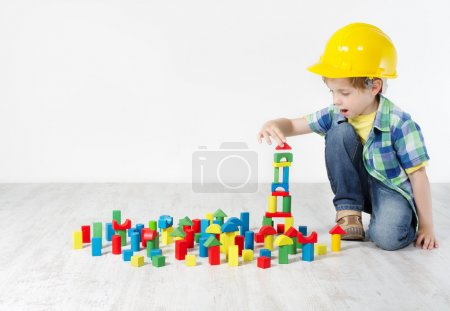 Photo for Kids Play Room, Child in Hard Hat Playing Building Blocks Toys. Development and Construction Concept - Royalty Free Image