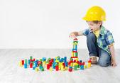 Dětský pokoj, dítě v čepice, hrající hračky stavebnice
