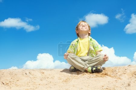 Happy Child Positive Think, Boy Sitting in Yoga Lotus position over blue sky on the top. Kid  Happiness and freedom concept.