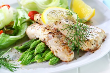 Photo for Delicious fried fish on green asparagus with salad - Royalty Free Image