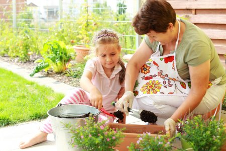 Photo for Elderly woman and child replanting flowers for better growth - Royalty Free Image