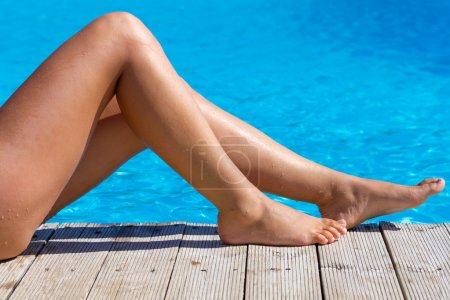 Photo for Sexy female legs at blue water of swimming pool - Royalty Free Image