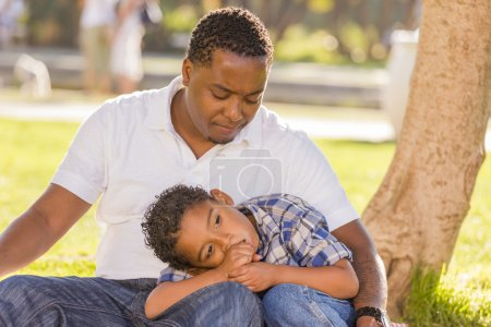 Photo for African American Father Worried About His Mixed Race Son as They Sit in the Park. - Royalty Free Image