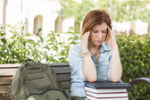Female Student Outside with Headache Sitting with Books and Back