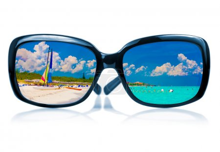 Sunglasses reflecting a tropical beach
