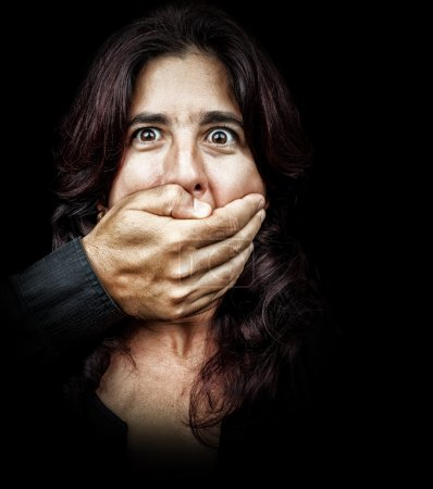Woman with a hand covering her mouth